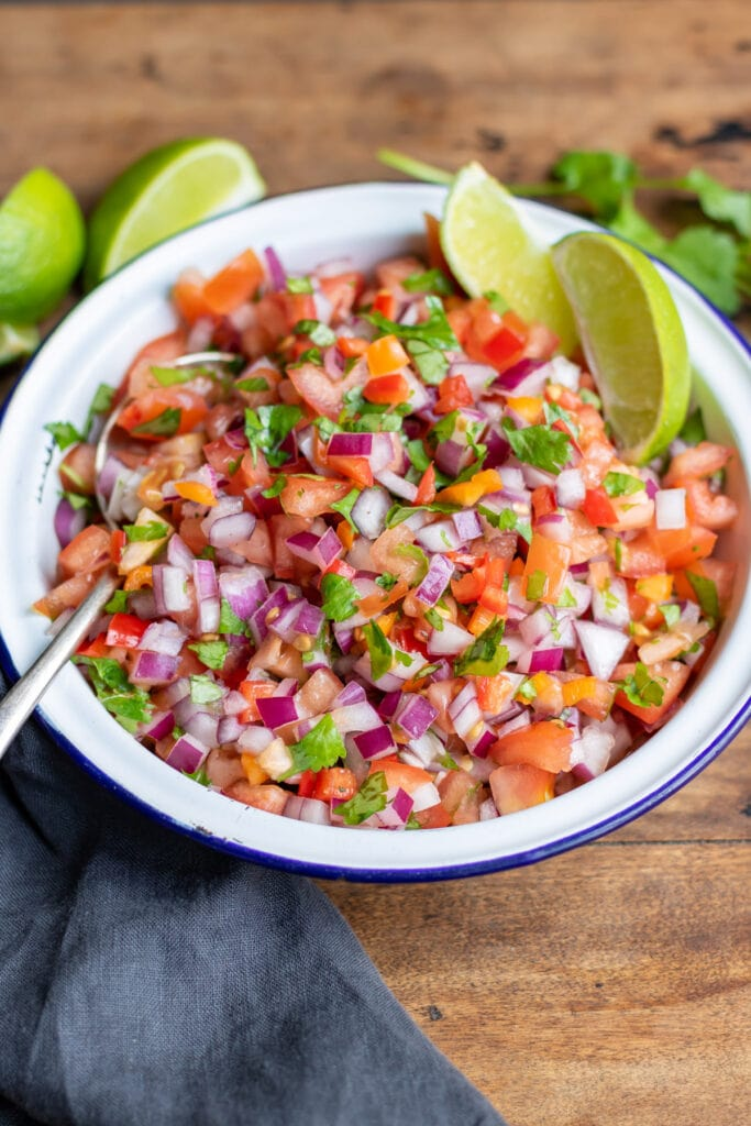 Serving dish of habanero salsa with lime wedges around it.