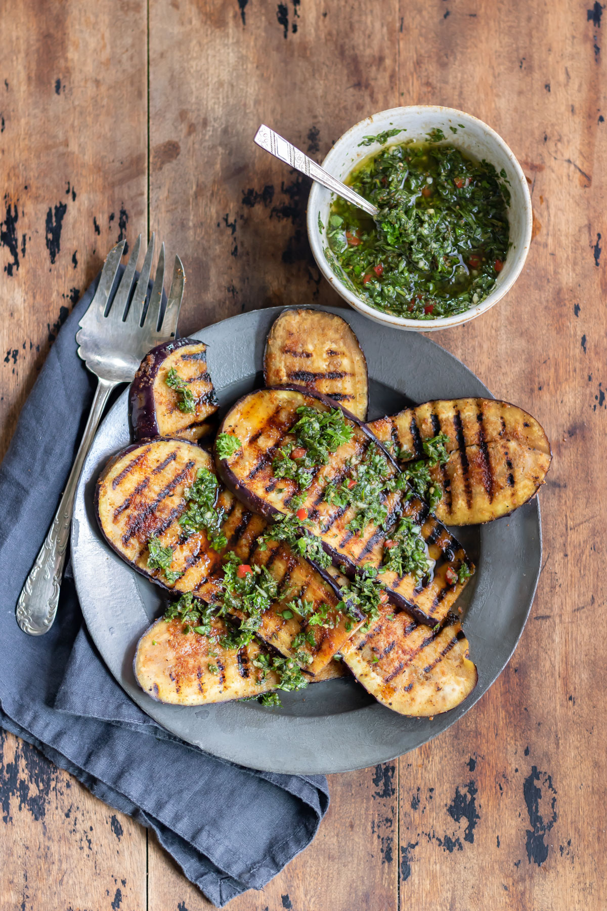 Wooden table with a plate of grilled eggplant steaks.