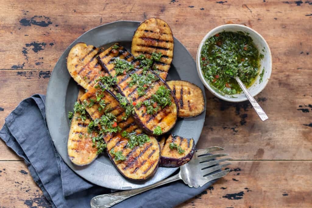 Wooden table with a plate of grilled eggplant steaks and a bowl of chimichurri.