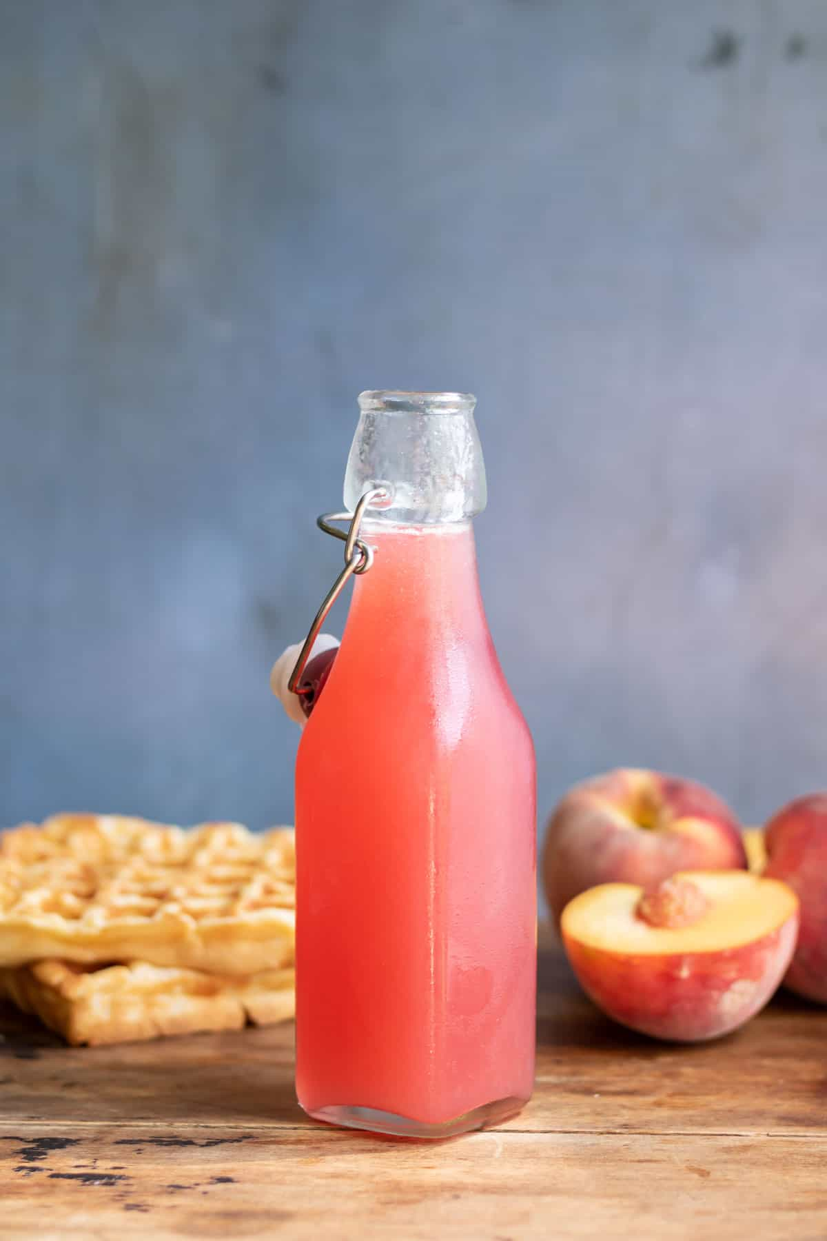 Bottle of fresh peach syrup next to peaches and waffles.