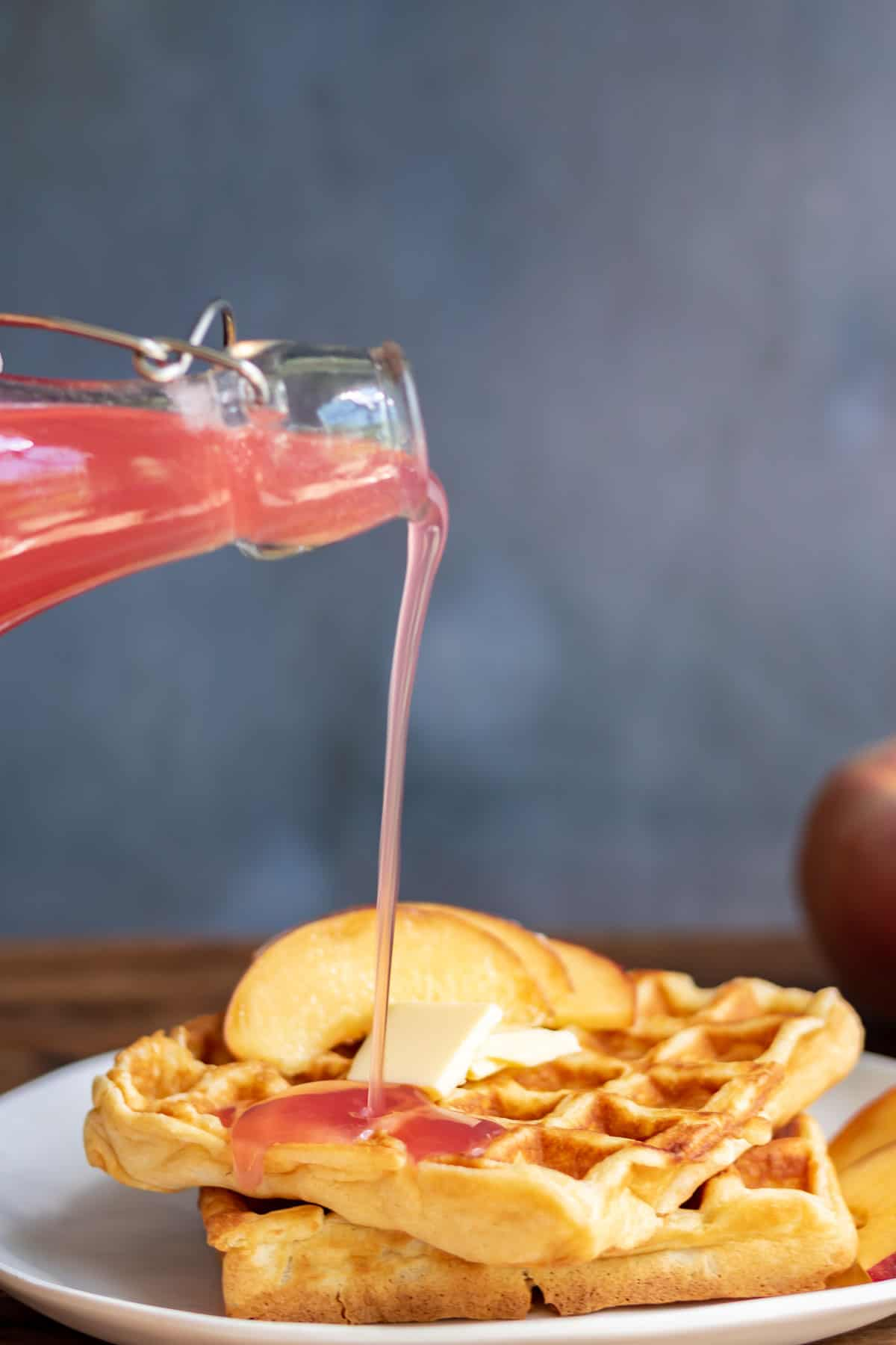 Peach syrup being drizzled onto waffles.