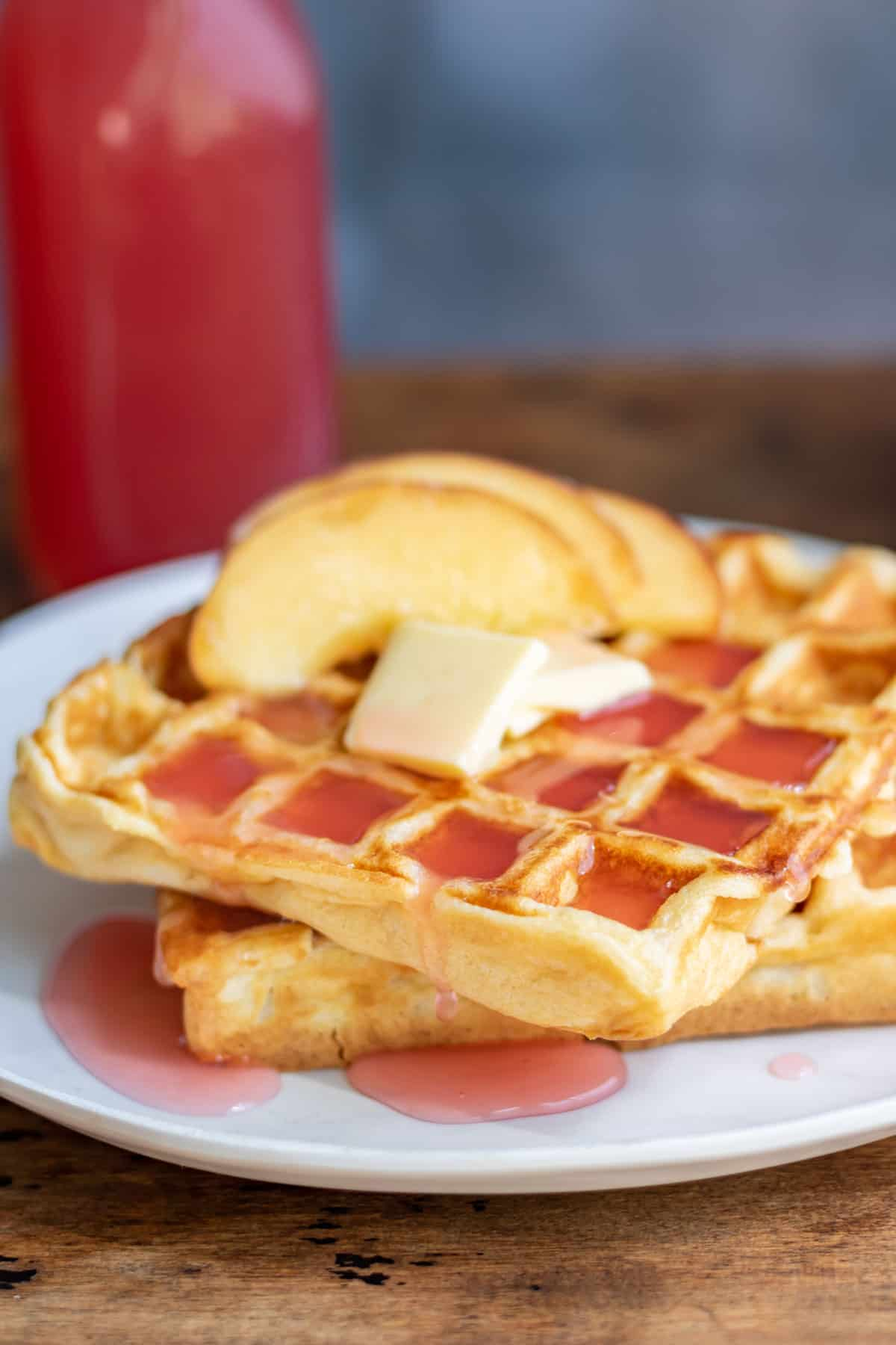 Waffles with butter, sliced peaches and peach syrup.