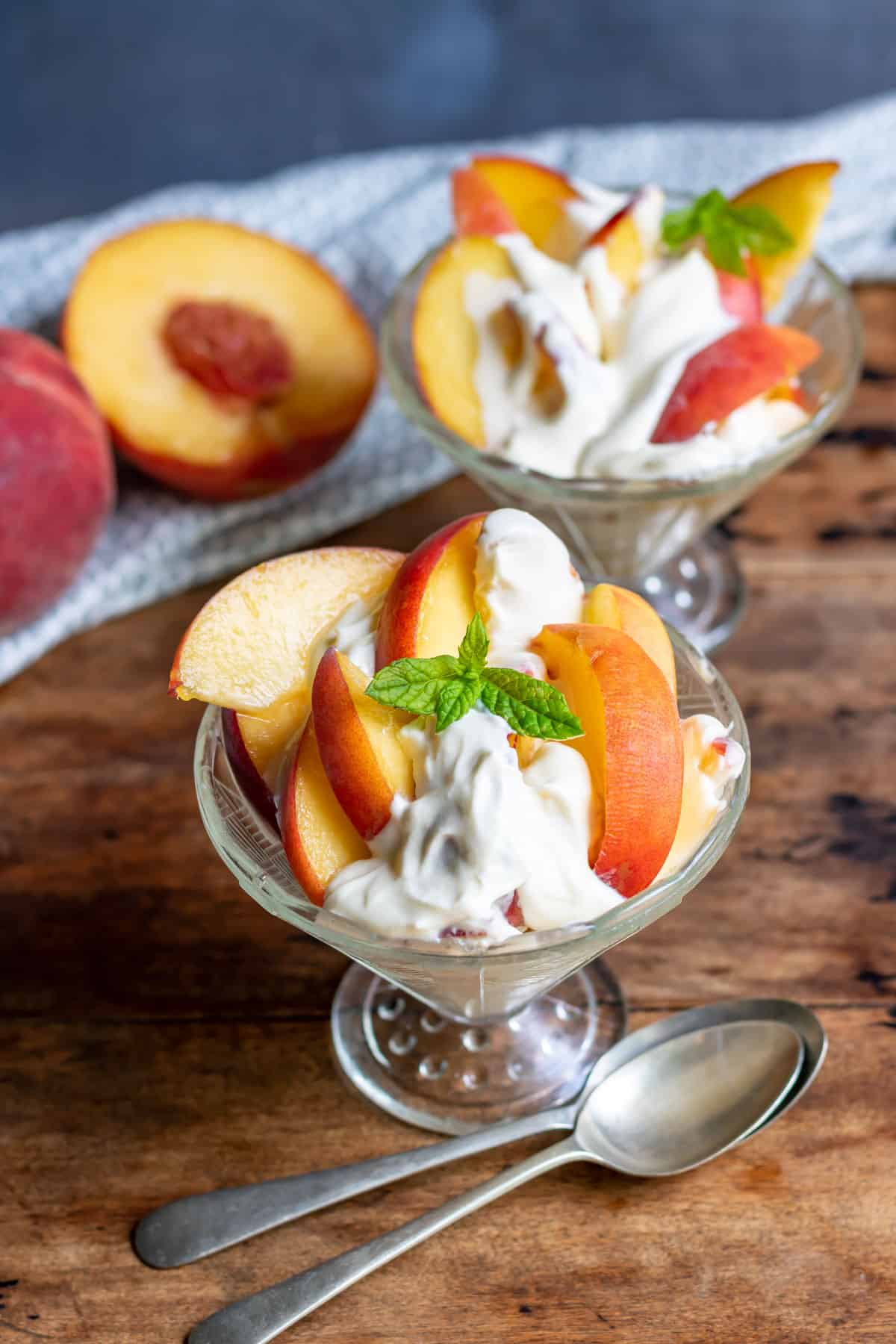 Glass dishes with peaches drizzled in a vanilla cream.