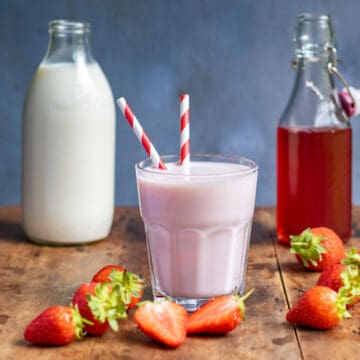 Glass of strawberry milk, bottle of milk and bottle of strawberry syrup, on a wooden table.