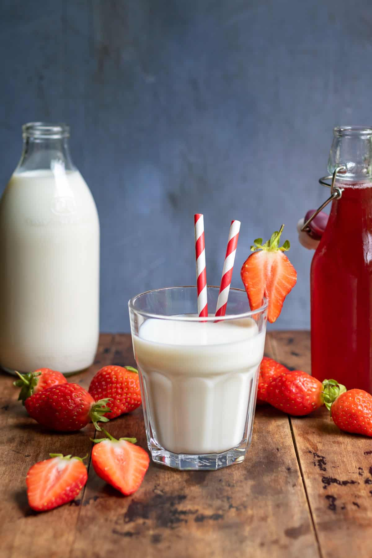 Table with glass of milk and strawberries.